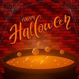 Brick wall and Halloween cauldron with orange potion Stock Images