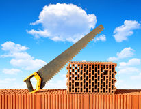 Brick wall with handsaw on bricks. Stock Image