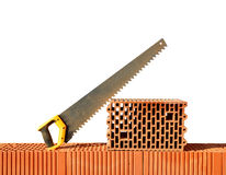 Brick wall with handsaw on bricks. Royalty Free Stock Photos