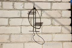 On the brick wall hanging flower stand. Shadow royalty free stock photos