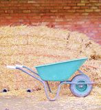 Brick wall with hay bales and wheel barrow Royalty Free Stock Photos