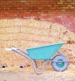 Brick wall with hay bales and wheel barrow Royalty Free Stock Photos