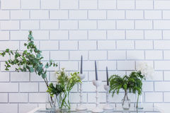 Brick wall interior with cafe table Candles, plant and vase of f. Lowers Royalty Free Stock Photography