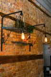 Brick wall with lamps and inscription in unusual cafe. Female visited new coffee house and took picture of brick wall with flashlights, wooden slats, black stock image