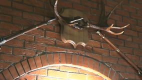 Brick wall with lamps, moose antlers, two guns stock footage