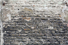 Brick wall with layers of weathered stucco and tar. Stock Images