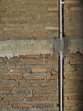Brick wall with metal pipe. Royalty Free Stock Photography