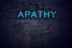 Brick wall and neon sign with text apathy.  royalty free stock photography