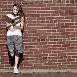 Brick Wall Notebook Girl. Beautiful young girl reading notebook against a brick wall royalty free stock photo
