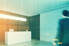 Brick wall office, white reception desk side. man Stock Photo