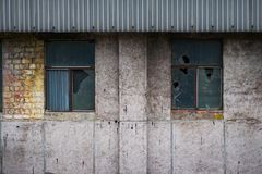 Brick wall of an old abandoned factory building with cracks on the plaster and windows. Royalty Free Stock Photos