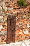 Brick wall of old house with a wooden door Stock Photography