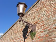 Brick wall with old lantern. Photography of old lantern on a brick wall, sunny day, blue sky in background Royalty Free Stock Photo