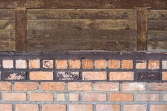 Brick wall. The old wall lower part of brick and the upper wood sheet Stock Images