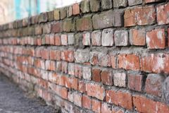 Brick wall of old red brick. Texture of stone and cement. Old paint. Rows and alternation royalty free stock photos