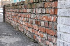 Brick wall of old red brick. Texture of stone and cement. Old paint. Rows and alternation stock photos