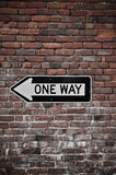 Brick Wall with One Way Sign Stock Photos
