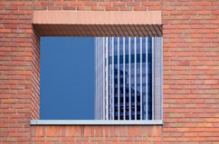 Brick wall with opening. Red brick wall with opening with view of skyscraper behind Stock Image