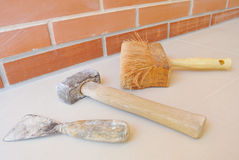 Brick wall with paintbrush. Brick wall, hammer and a paintbrush Royalty Free Stock Photography