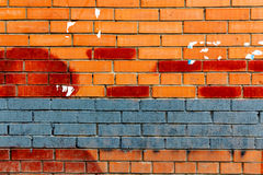 Brick wall painted blue and red paint with traces of ads. Abstract background Stock Photos