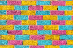 Brick wall painted in bright yellow, blue and pink colors Royalty Free Stock Images