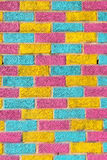 Brick wall painted in bright yellow, blue and pink colors Stock Images