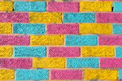 Brick wall painted in bright yellow, blue and pink colors Royalty Free Stock Photo
