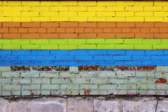 Brick wall painted with colored dyes in the form of stripes: yellow, brown, green and blue. Royalty Free Stock Photos