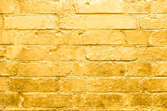 Brick wall  painted in gold,  golden graffiti background Stock Photos