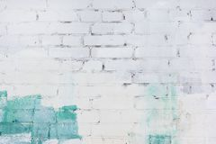 The brick wall is painted with green and white paint. Background with space for text, texture. The brick wall is painted with green and white paint. Unusual stock photography