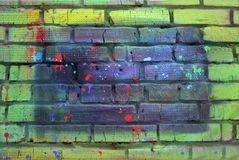 Brick wall painted with multicolored paint stock photos