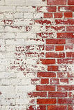 Brick wall. Partly red partly white, scattered paint Stock Photos