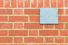 Brick wall pattern with blue metal plaque Stock Image