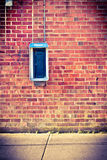 Brick wall with payphone Royalty Free Stock Image
