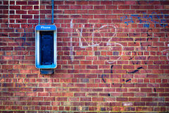 Brick wall with payphone. Grungy urban background of a brick wall with an old out of service payphone on it royalty free stock photography