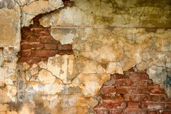 Brick wall with peeling plaster. In the old house Stock Images