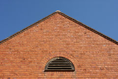 Brick wall with a pitched roof. And a blue sky stock photo