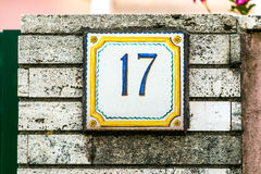 Brick wall with plate number seventeen. Old brick wall with tile plate number seventeen - classical facade Royalty Free Stock Photo