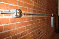 Brick wall with a power outlet and pipe Stock Photography