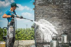 Brick Wall Pressure Washing. Brick House Wall Pressure Washing with Special Cleaning Detergent. Caucasian Men in His 30s. Taking Care of the Building Elevation stock photo