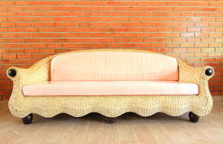 Brick wall with a Rattan sofa Stock Image