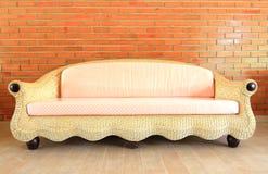 Brick wall with a Rattan sofa Stock Image