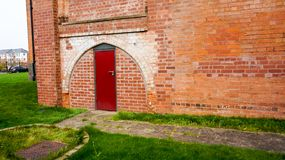 Brick wall with red door under arch Stock Photo