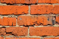 Brick wall of red uneven bricks. Close-up.  royalty free stock image