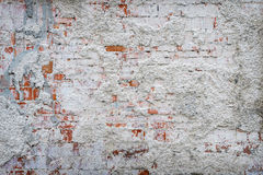 Brick wall remains of old plaster. Brick wall of the house with the remains of old plaster and white paint. grunge textured background Royalty Free Stock Images