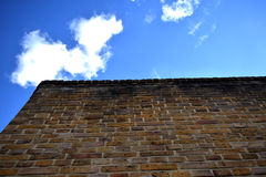 Brick wall set against blue sky with clouds Stock Photography
