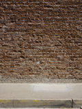 Brick wall and sidewalk. Textured red brick wall and concrete sidewalk Stock Photos