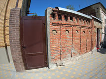 Brick wall with a solid metal door in a city street Stock Photo