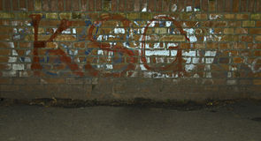 Brick wall. With sprayed graffiti and letters Stock Images