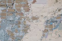 Brick wall with stains of old paint and peeling plaster. stock image